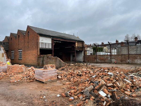The old Batten Street Premises during demolition showing the collection of the bricks for reuse.