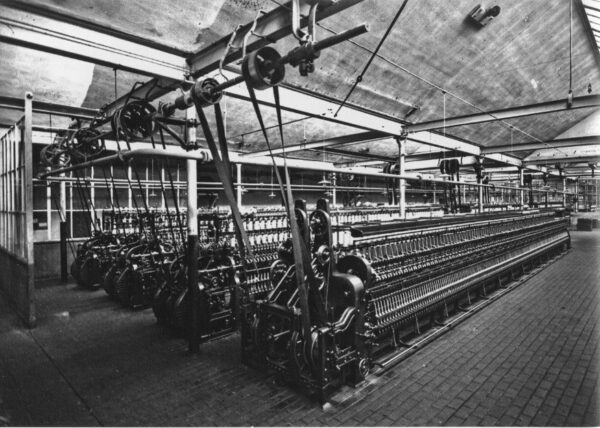 A textile mill showing a set of 4 cotton spinners being powered by line shaft power transmission.